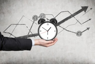 A businessman's hand holds an alarm clock. There is a growing line charts behind the alarm clock. A concept of time management or billing services in legal or consulting company.