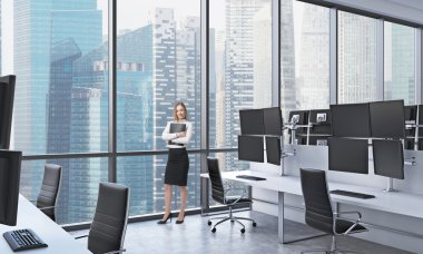 A young lady in formal clothes holds a black document folder in the modern panoramic office in Singapore. White tables equipped with modern trader's stations and black chairs.