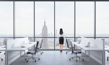 Rear view of a brunette who is looking out the window in the modern panoramic office with New York view. White tables equipped with modern laptops and black chairs.