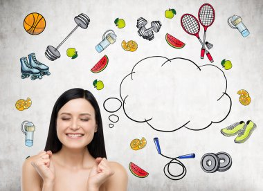 Dreaming beautiful brunette lady is thinking about her choice of sport activity. Colourful sport icons are drawn on the concrete wall. A concept of a healthy lifestyle.