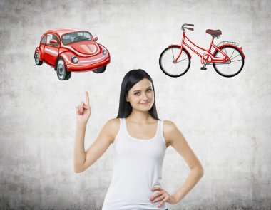 A beautiful woman is trying to chose the most suitable way for travelling or commuting. Her choice is a car. Two sketches of a car and a bicycle are drawn on the concrete wall.