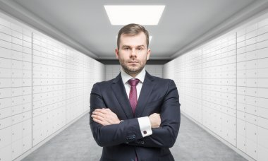 A private manger of a bank with crossed hands is standing in a room with safe deposit boxes. A concept of storing of important documents or valuables in a safe and secure environment.