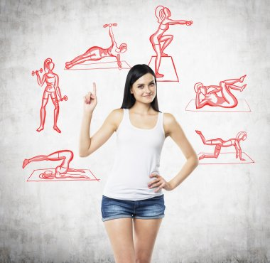 A beautiful brunette woman in a white tank top and denim shorts who is pointing out her finger up. Red crossfit icons are drawn on the concrete wall.
