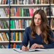 Serious young girl with loose long dark hair  sitting at a desk — стоковое фото #91395500