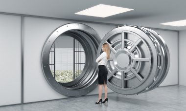 young lady standing in front of a big unlocked round metal safe