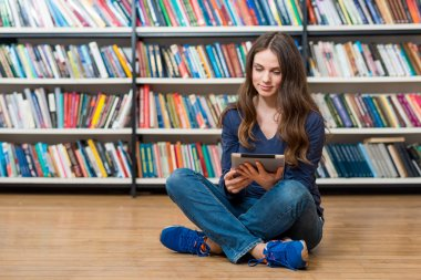 smiling young girl sitting on the floor in the library with cros