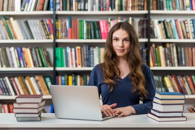 smiling young girl sitting at a desk in the library working with