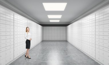 A beautiful private manger of a bank is standing in a room with safe deposit boxes. A concept of storing of important documents or valuables in a safe and secure environment.