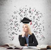 nő ül a pultnál, a könyvek körül gondolkodás oktatás