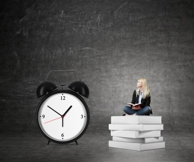 woman sitting on pile of books, big alarm clock  right