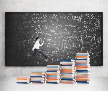 Young man with a folder in hand running up stairs made of piles of books of different size, blackboard with notes at the concrete background.