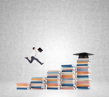 Young man with a folder in hand running up stairs made of piles of books of different size, graduation hat on the highest, concrete background.