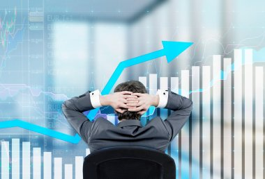 Relaxing businessman sitting on the chair with hands on the back of his head. Image of semi-transparent graphs in front.