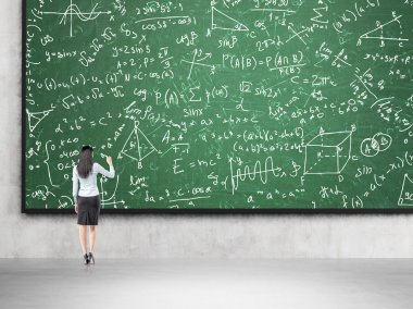 Woman solving problems on blackboard