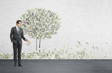 Young businessman with one hand in pocket holding a watering can pouring water on a drawn tree with dollars instead of leaves