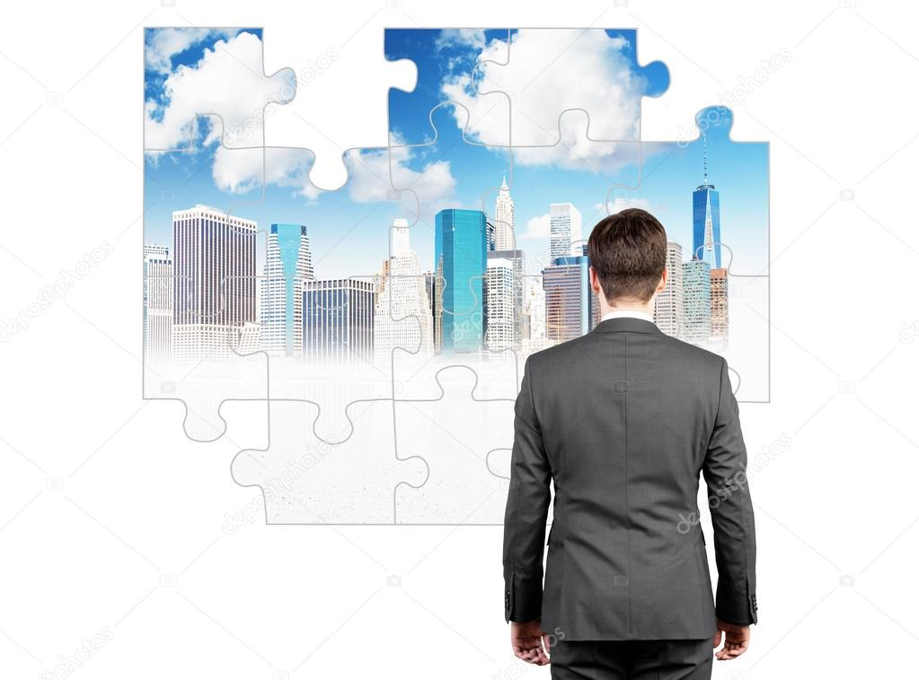 A businessman standing with a stiff back in front of a puzzle on the white wall with a picture of New York, several parts missing.