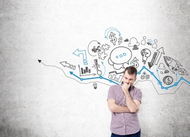 A young man with hand to the chin thinking and standing in front of a concrete wall with many different business icons drawn on it over a graph.