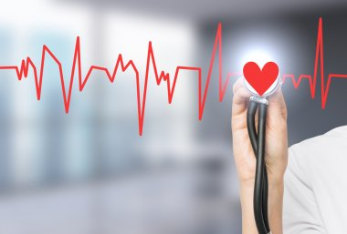 A hand listening to a red heart with a phonendoscope, the heart is a part of a cardiogram.