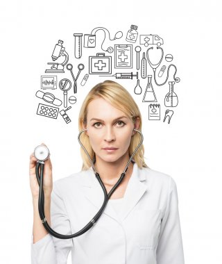 A young female doctor in a white smock holding a phonendoscope and standing in front of the white wall, many medical icons drawn on it.