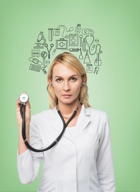 A young female doctor in a white smock holding a phonendoscope and standing in front of the green wall, many medical icons drawn on it.