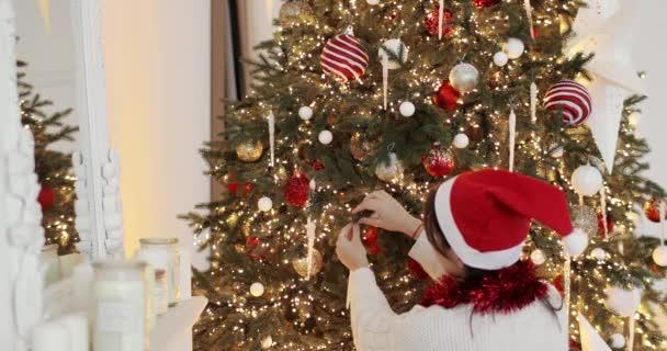 Mladá žena v červeném klobouku zdobí vánoční stromek s hračkami doma, pohled zezadu.
