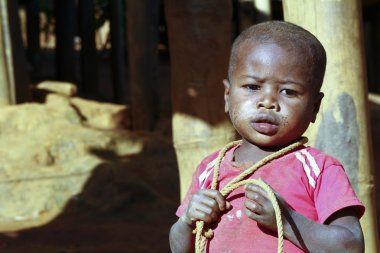 Poor african boy with a string - is he trying to attempt a sueci