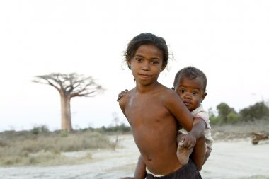 Madagascar-shy and poor african girl with infant on her back - p