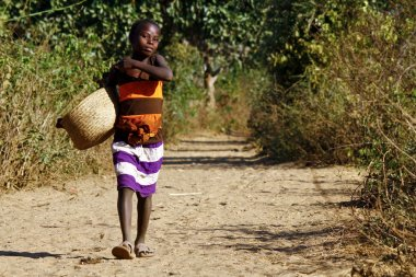 Poor african girl walking the african path with basket in hand