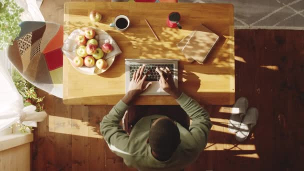 Top down shot of Afro-American man typing on laptop at wooden table with apples, coffee and notepads on it while working remotely from home