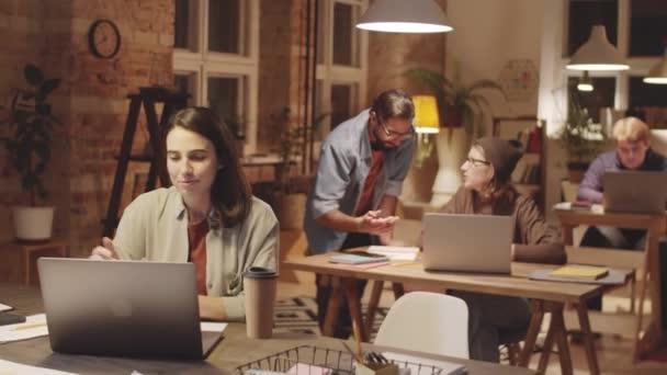 Fiatal gyönyörű üzletasszony ül íróasztal padláson padláson iroda és megvitassák a munkát keresztül online video hívás laptop, miközben késő este dolgozik
