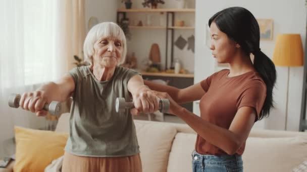 Veselý senior žena cvičení s činky s pomocí mladé ženy pečovatelky v obývacím pokoji doma