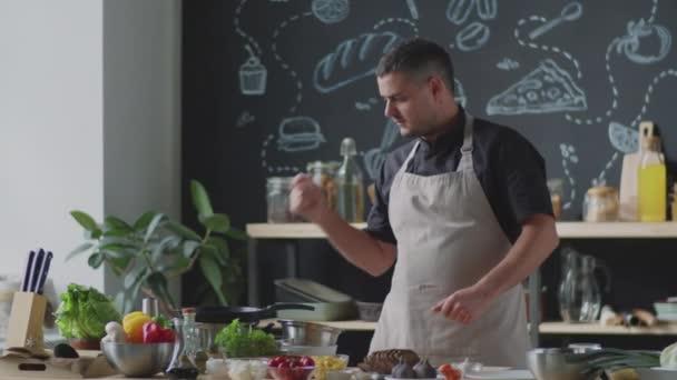 Männlicher Koch in Schürze spricht vor der Kamera, stellt Pfanne auf Herd und wirft dann Brotscheiben hinein, während er Online-Kochkurs in der Küche für Lebensmittel-vlog aufzeichnet