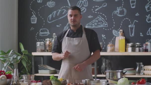 Professionelle männliche Köche in Schürze riechen Brot, werfen Avocado und sprechen in die Kamera, während Videoaufnahmen für kulinarische Blog in der Küche