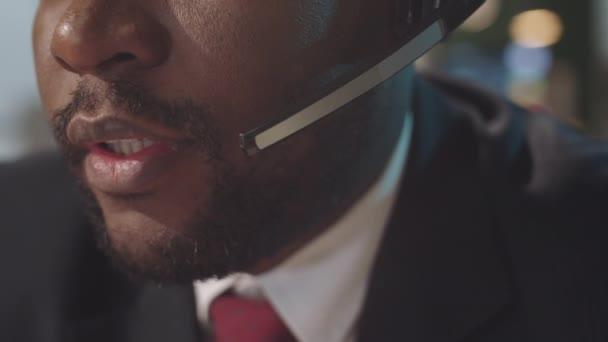Közelkép alsó része az arc fekete üzletember vezeték nélküli headset beszél az online hívás az irodában