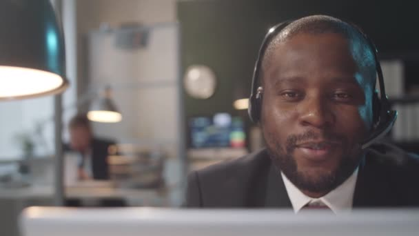 Követés felvétel afro-amerikai üzletember vezeték nélküli headset és formalwear ül irodai íróasztal és beszél online video hívás laptop