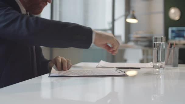 Közelkép kaukázusi üzletember kézfogásáról, amint aláírja a szerződést, és kezet fog afro-amerikai partnerével, miközben az irodai asztalnál ül.