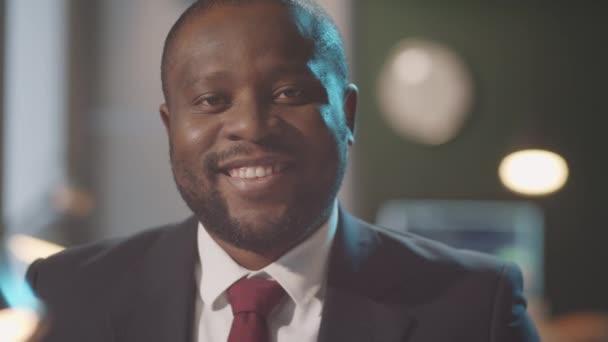 Egy vidám afro-amerikai üzletember portréja formális öltözetben, ahogy a kamerába néz és mosolyog.