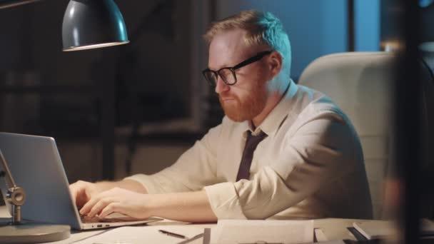 Szakállas, kaukázusi üzletember, hivatalos öltözetben és szemüvegben gépel a laptopján az irodai asztalnál, majd este túlórázás közben pózol a kamerának.