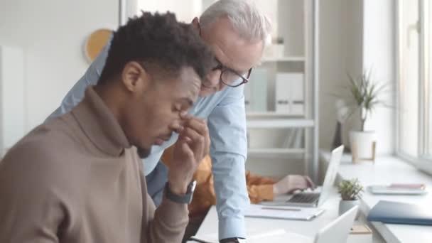 Derékig érő felvétel arról, hogy a fehér férfi menedzser odasétál a fiatal afro-amerikai gyakornokhoz, megnézi a munkáját a laptopon, beszél, hallgat, visszajelzést és tanácsot ad neki.