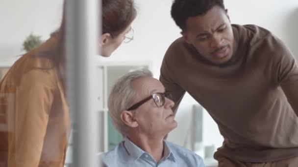 Nahaufnahme eines frustrierten älteren kaukasischen Mannes, der im Büro am Schreibtisch sitzt und sich bei multinationalen Kollegen über Arbeitsprobleme beschwert, und eines schwarzen Mannes, der auf den Laptop schaut und Ratschläge gibt.