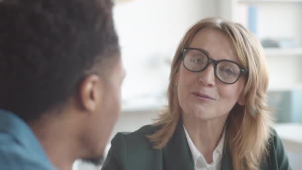 Közelkép egy mosolygós középkorú fehér HR-es nőről szemüvegben és üzleti dzsekiben, aki afro-amerikai junior munkatárssal beszélget az irodai értékbecslés során.
