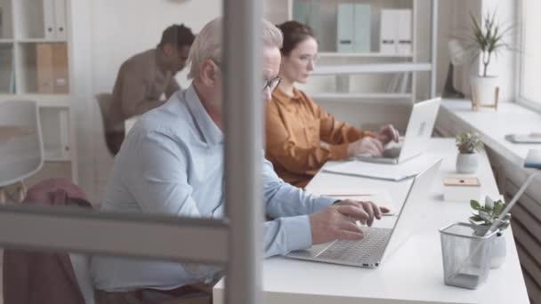 Deréktól felfelé íves lövés fókuszált fehér férfi ősz hajjal, szemüvegben ül az íróasztalnál az irodában és gépel a laptopon, és változatos fiatal kollégák dolgoznak a háttérben