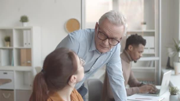 Közepes nyomkövető felvétel középkorú kaukázusi férfi menedzserről, aki odasétál egy fiatal női alkalmazotthoz, aki laptopon dolgozik az asztalnál, nézi a képernyőjét, megmagyarázza a hibát és segít a problémában.