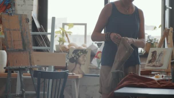 Schnappschuss einer professionellen Künstlerin, die sich bei der Vorbereitung auf den Arbeitstag im Atelier Schürze anzieht
