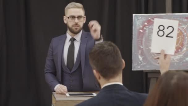 Profi férfi árverező, aki nézi, ahogy a közönség emeli a lapátjait, licitál és licitál az aukción, miközben a modern műalkotások mellett áll a terítéken.
