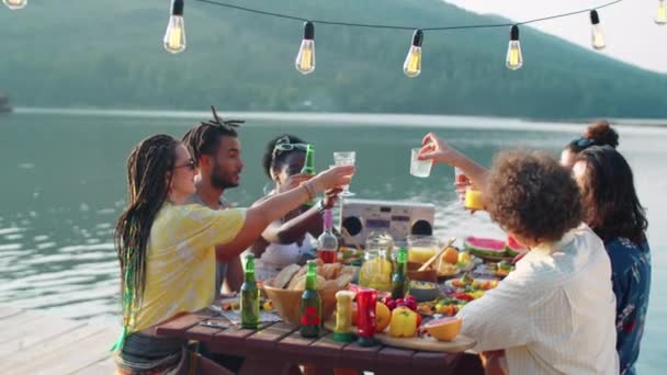 Company of young multiethnic friends sitting at dinner table on lake pier, smiling and clinking glasses together in toast while having outdoor party in nature