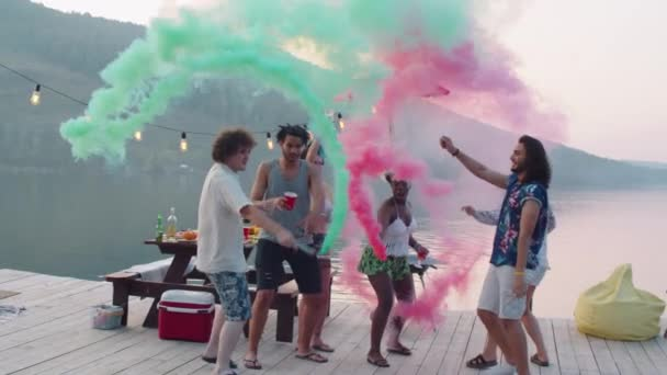 Company of young happy multiethnic friends dancing with colored smoke bombs on wooden pier while having lake party on summer evening