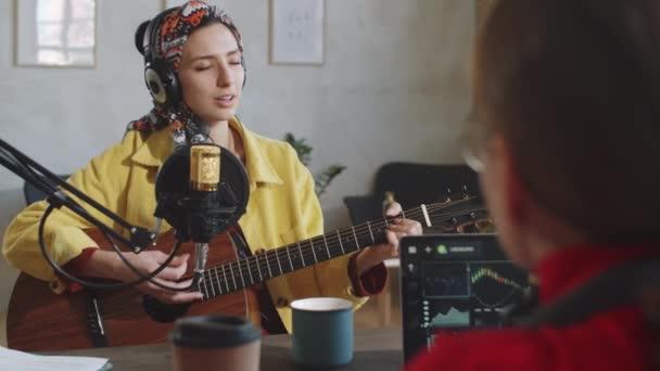 Über der Schulter Aufnahme einer jungen Frau mit Kopfhörer, die Gitarre spielt und ins Mikrofon singt, dann lächelt und sich bei der Podcast-Moderatorin bedankt, die ihr während des Livestreams applaudiert