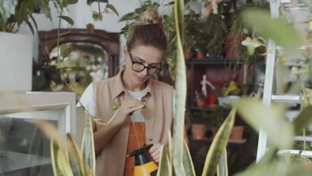 Kavkazská žena květinářství v ležérní oblečení a brýle pomocí láhve s čerpadlem při postřiku rostlin v květinářství