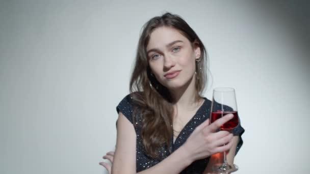 Studio portrét mladé krásné ženy v okouzlující držení vína sklenice a pózování pro fotoaparát
